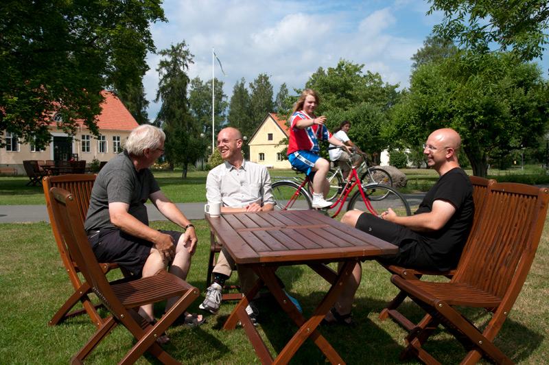 Hasse Larsson, Erik Hellsten och Ola Gustafsson sitter i solen och ger fanken i börsutvecklingen. Cyklisterna Jesper Öberg och Max del Rio Diaz håller med.